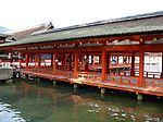 A wooden roofed corridor on stilts over water with red beams and red handrails.