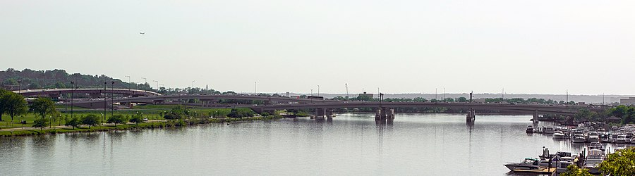 Photograph of a bridge gently curving over a wide river, with a marina to the right and flyovers to the left.