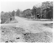 A grayscale view of a rural dirt road with a building visible to the right