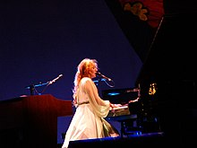 A woman with red hair in a white dress, playing a piano and singing into a microphone.