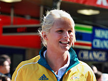 Young woman with bleached blonde hair, short and tied up, smiles. She is wearing a yellow tracksuit with a green collar, with the logo of Adidas and the coat of arms of Australia visible.