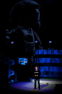 A man stands on a large stage, talking to the audience. Behind him is a flatscreen television displaying the game's title menu; behind that is a large representation of an ODST.