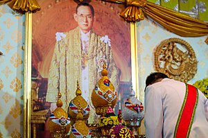 Lèse-majesté - A government officer pays respect to the portrait of King Bhumibol Adulyadej of Thailand.
