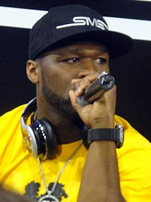 An African-American man, wearing a yellow shirt and baseball cap, speaks into a microphone.