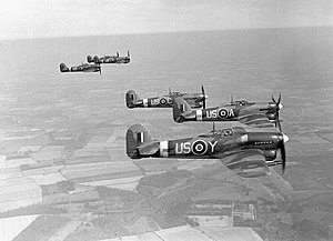 "No. 56 Squadron RAF - Two flights in formation. Sqn Ldr Pheloung leads in US-A. By 1943 these ""vics"" of three were only used to impress photographers. This photo appeared in 'Flight', 6 January 1944."