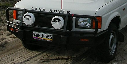 A bullbar on a Land Rover Discovery fitted with spotlights and a sand flag.