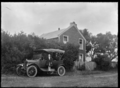 A car with four people parked outside a two storied house at Kaitoke, 1923 ATLIB 299526.png