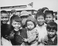 "A new market for ""Tinh Thuong."" Children gather before the market which was built with assistance from the government of - NARA - 541851.tif"