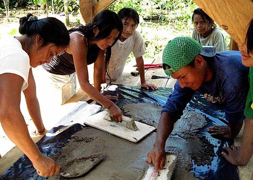 jovenes y mujeres achuar trabajando cemento
