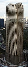 Aerial view of a brown and beige, rectangular, window-dotted high-rise