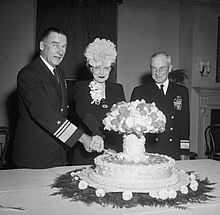Blandy and his wife slice into a cake labeled Operation Crossroads, and shaped like a mushroom cloud, while Admiral Frank J. Lowry looks on, November 7, 1946.