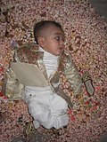 An infant on the top of a mound of sweets.jpg