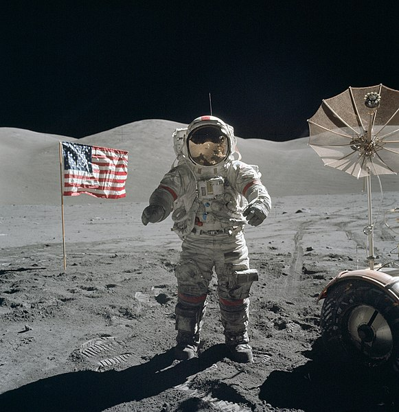 Apollo 17 astronaut Gene Cernan on the moon, flanked by an American flag and the lunar rover
