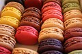 A variety of colored macarons including yellow, red, orange, green, blue, and brown.
