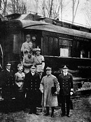black and white photograph of five men in military uniforms standing side-to-side in front of a railcar. Four men are disembarking behind them.