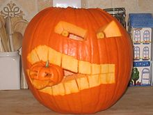 A jack-o-lantern carved with a face that is biting a smaller jack-o-lantern