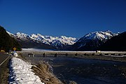 photo of a bridge over a river, with snow capped mountains in the background