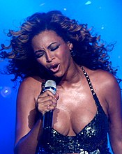 The upper body of a woman is shown as she sings into a microphone