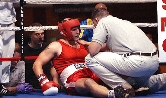 A boxer was knocked out, and is being inspected by a ring doctor.