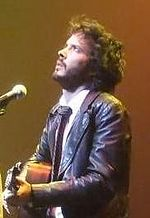 A man is performing with a microphone while playing a guitar. He wears a leather jacket and a white shirt. He has long black hair and a beard.