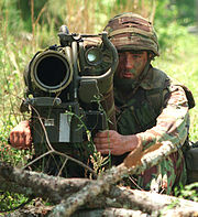 Colour photograph of a marine with an anti-tank weapon pointed at the camera.
