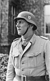 A man in semi profile wearing a military uniform, steel helmet and a neck order in the shape of a cross.