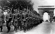 Soldiers walking down Champs-Élysées, with Arc de Triomphe in the back