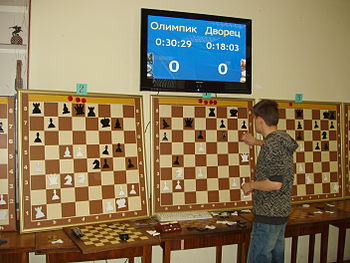 A man looks at three large chessboards on a wall with different positions