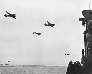 Utah Beach -  C-47 Skytrains with paratroops above a landing craft.