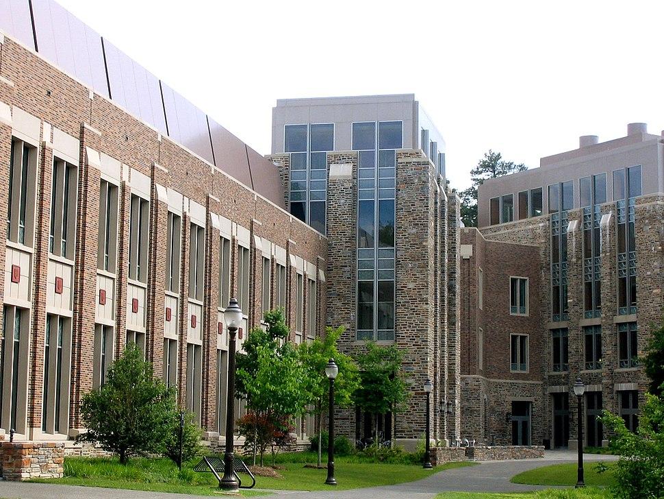 A four-story brick and stone building alongside pedestrian path