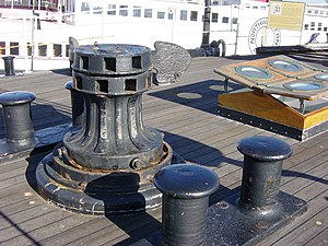 Capstan (nautical) - A capstan on a sailing ship. The upper portion is operating the anchor windlass below in the Forecastle