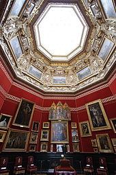 Vue en contre-plongée de la salle octogonale décorée de tentures rouges et de tableaux et surplombée d'une verrière