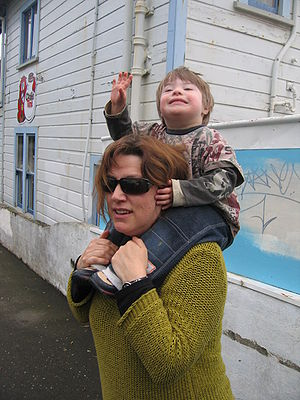 a child (with Down syndrome) piggy-backing on ...