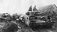 tanks moving along a muddy road beside a low building