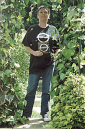 A middle-aged woman stands on a path amidst green vegetation, under bright sunlight. She wears a black T-shirt with a white logo, and holds a small piece of black card which carries the same logo. She has blue jeans, and white shoes. Her hair is cut short. She is looking slightly upward, over the head of the photographer.