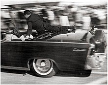 Ike Altgens's photo of the Presidential limousine taken between the first and second shots that hit President Kennedy. Kennedy's left hand is in front of his throat and Mrs. Kennedy's left hand is holding his arm.