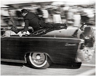 Assassination of John F. Kennedy - Secret Service Special Agent Clint Hill shields the occupants of the Presidential limousine moments after the fatal shots. Note the effect of panning in the photograph.