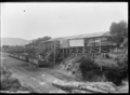 Coal being loaded into railway wagons through chutes, at Saddle Hill, Dunedin. ATLIB 292078.png
