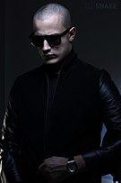 A man with a shaved head wearing black sunglasses, dark clothing and a watch