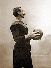 Bild von Gallaher, der seine schwarze Rugby-Uniform trägt und einen Fußball umklammert.