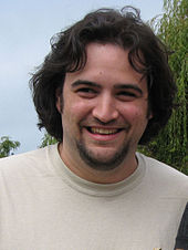 Causcasian man with medium-length dark brown hair and a beard smiles for a camera. The man is wearing a gray t-shirt with an image of evolution from a monkey to a pirate