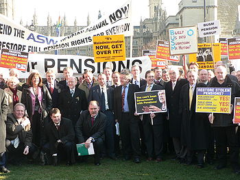 A group of people holding placards standing in front of the Palace of Westminster