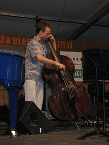 A jazz bassist playing double bass using an amplifier and speaker cabinet for a show.