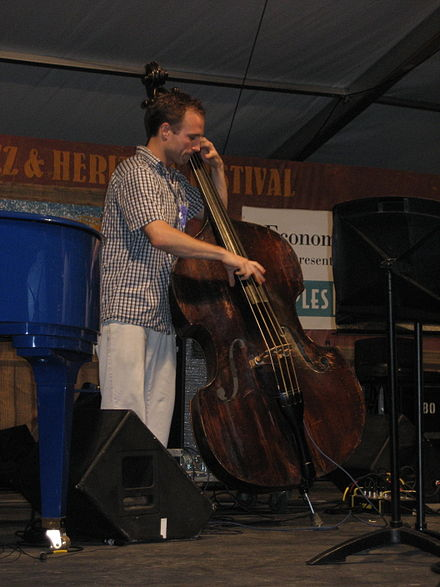 A jazz bassist performing on an upright bass, using an amplifier and speaker to augment the instrument's natural volume EconHall4May07Stringbass.jpg