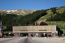 Building facing a large mountain with two openings for the traffic, visible on the roof of the building are large ventilation hoods