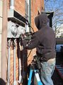 Electrician using screwdriver to install external panels for meters in NJ.JPG