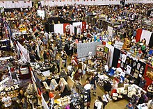 Photograph of the Expo in progress, taken from a high vantage point, showing crowds of attendees among booths arranged in a grid.