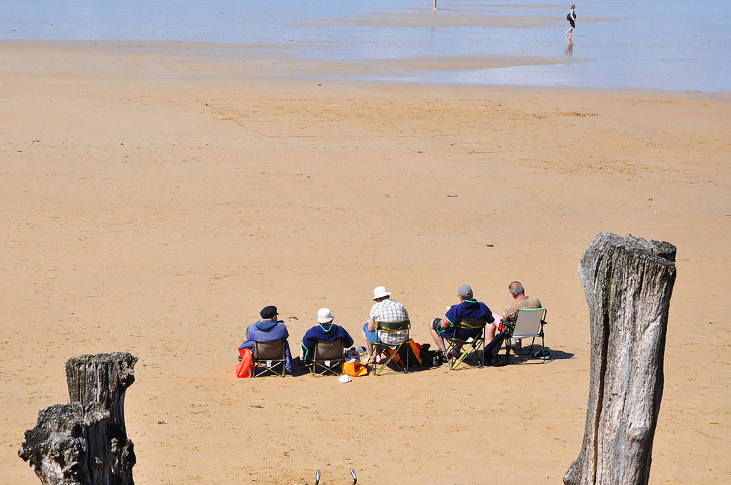 Elderly people sit on the beach.