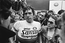 A man sweating and wearing a cycling jersey while being surrounded by several people.