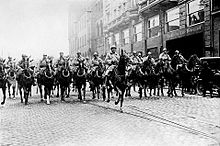 French cavalry marching down a street in formation.